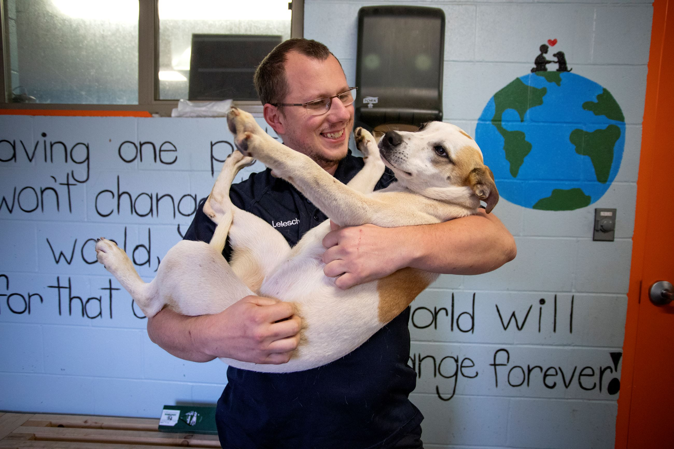 Justin Lelesch, the new animal services director holding and playing with a dog at the shelter