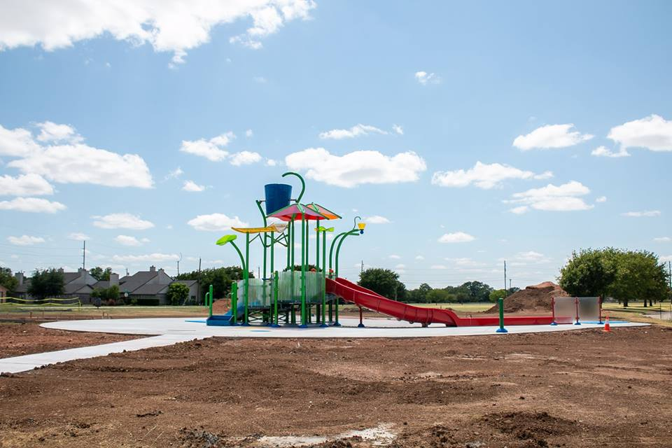 Colorful splash pad with multiple slides and a large bucket at the top for dumping water 2