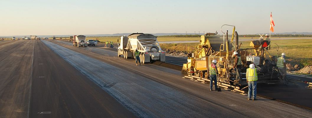 Construction Vehicles in a Line Working Up the Runway