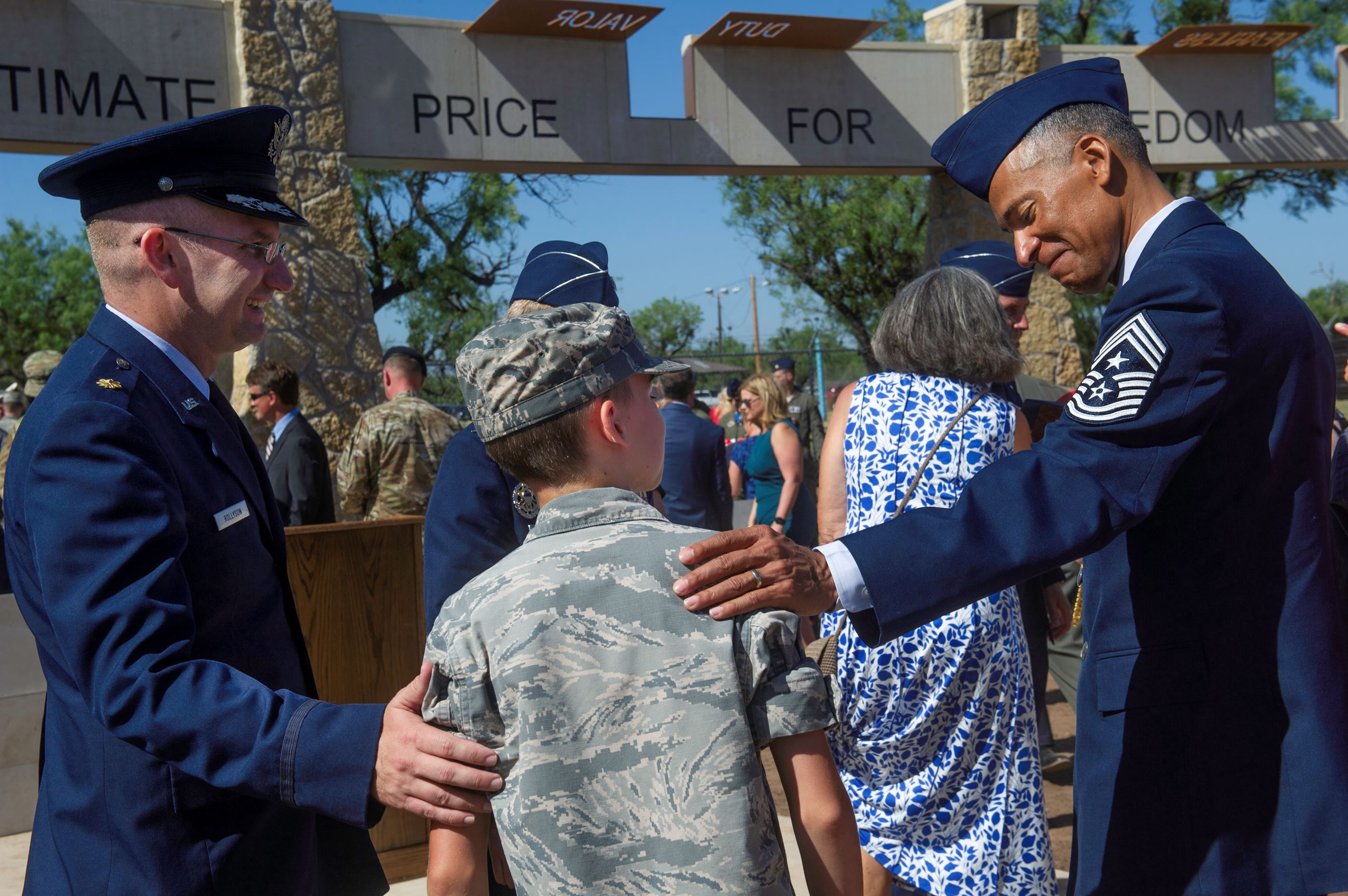 Two airmen greet a young man at the opening of the Dyess Memorial in 2019.