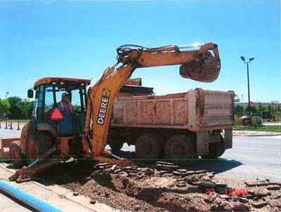 Backhoe and truck at water line construction site