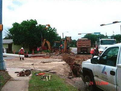 Workers, trucks, and machinery at water line construction site